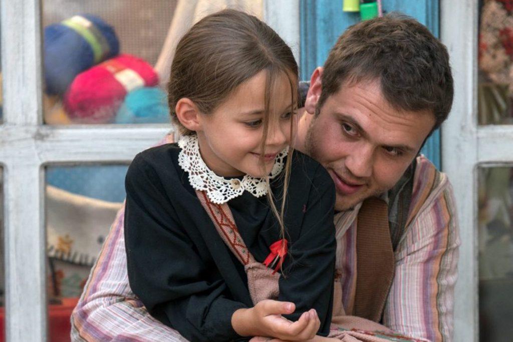 as personagens do filme Milagre na Cela 7, Memo e Ova, estão sentados em frente a uma loja. Ambos estão sorrindo e felizes.