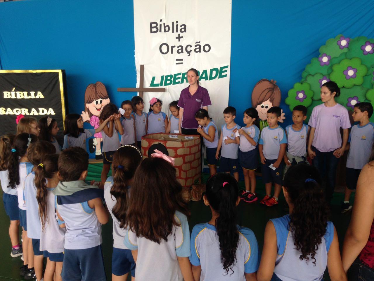"""Crianças depositam seus pedidos e agradecimentos no """"poço de oração""""."""