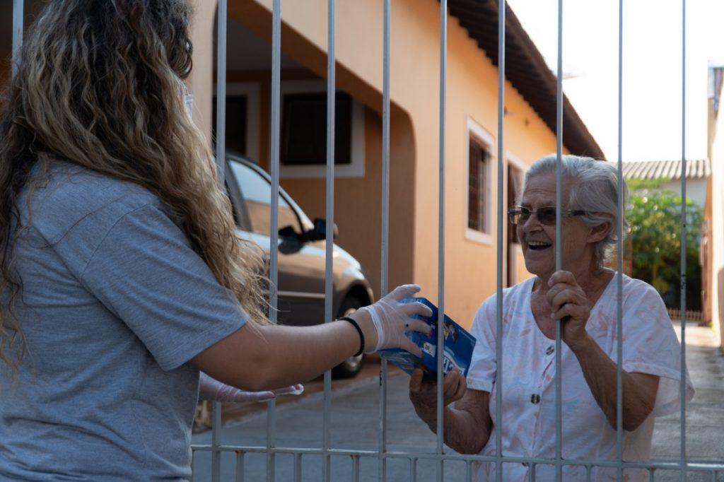 Estudante universitária entregando uma lembrança de páscoa para uma idosa em quarentena.