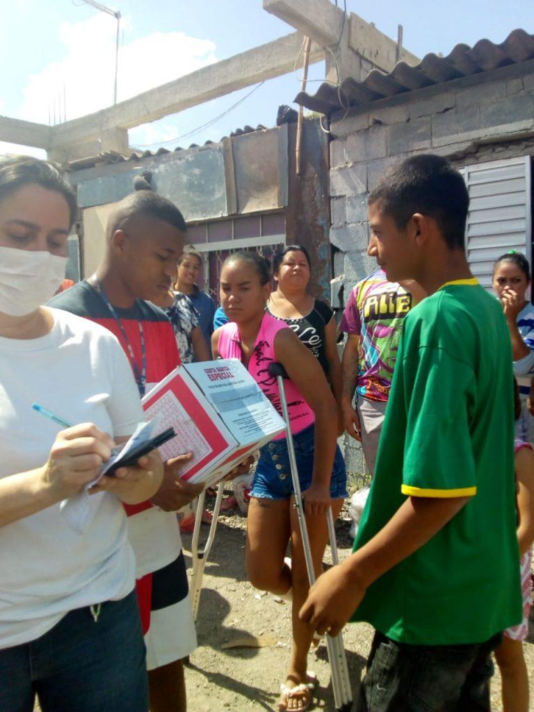Famílias da comunidade Portelinha recebendo doações de cestas básicas.