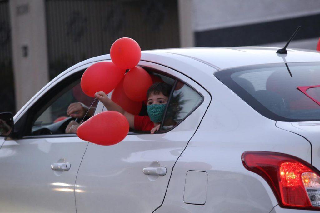 Criança na janela do carro segurando balões