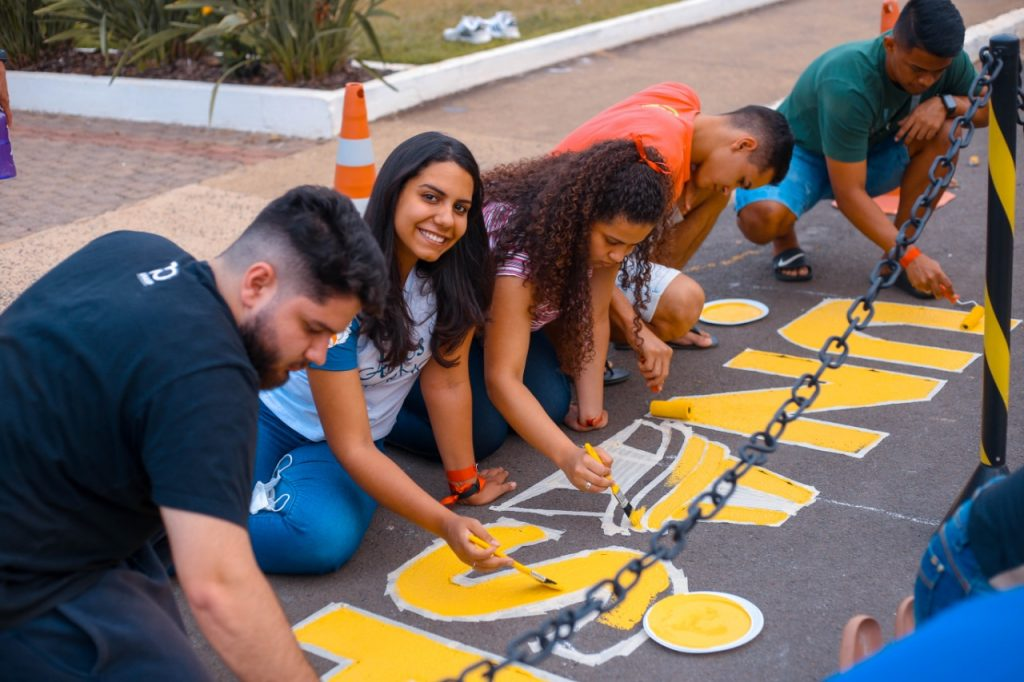 Jovens pintando o chão