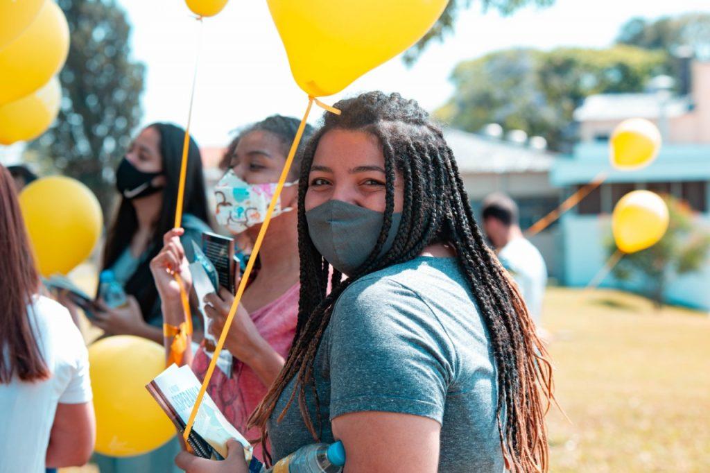 Jovem de máscara segurando balão amarelo