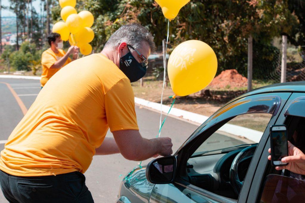 Professor entregando balão para aluno que está no carro.
