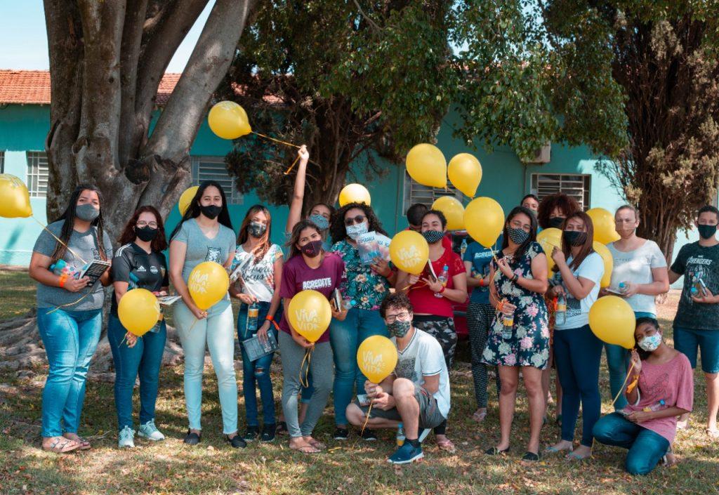 Pessoas de máscara e balões amarelos.