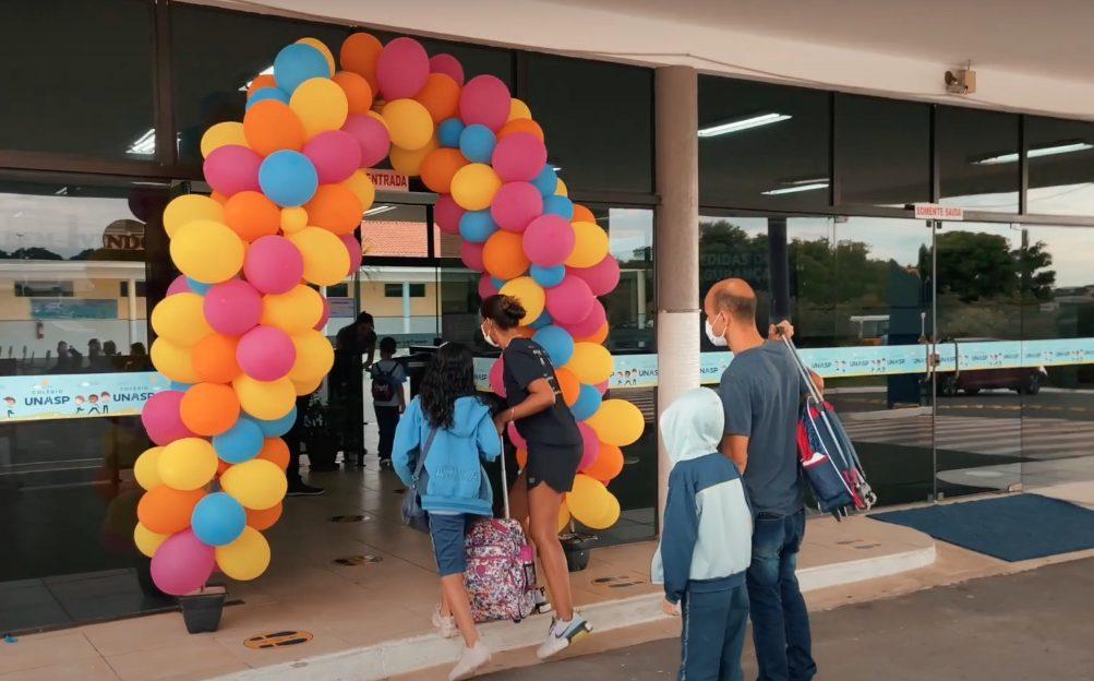 Pai acompanhando filho até a porta de entrada do colégio.