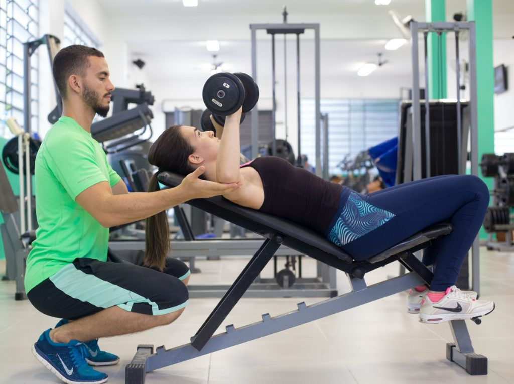 Treinador auxiliando aluna durante musculação na academia
