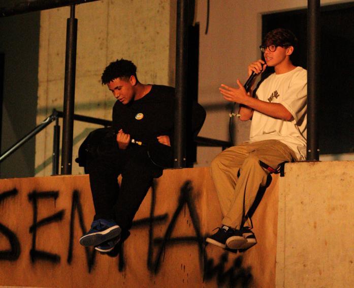 Dois jovens sentados em um muro, com uma faixa de papelão, onde está pichado a palavra Resenha.