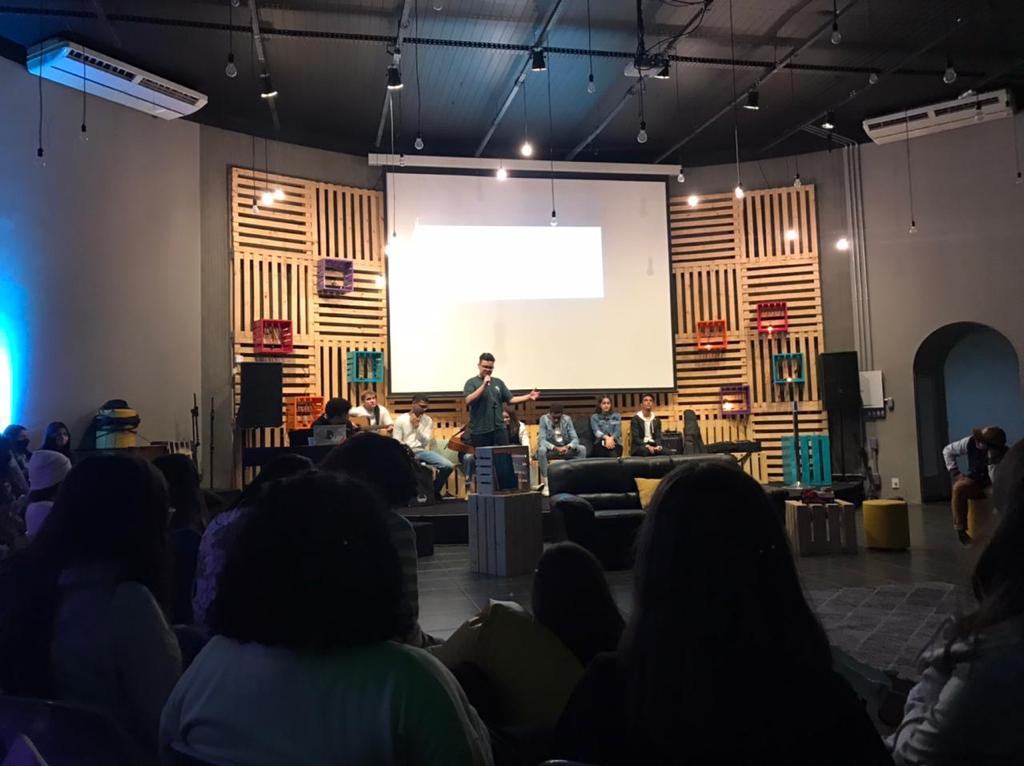 Jovem pregando para outros jovens em um auditório.
