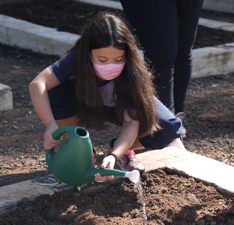 Criança molhando a terra com regador no Projeto Horta