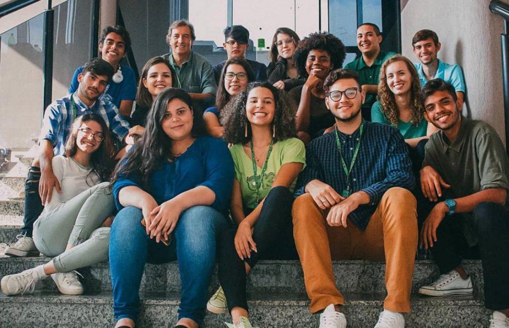 Jovens estudantes  sentados juntos nos degraus da escada da faculdade.