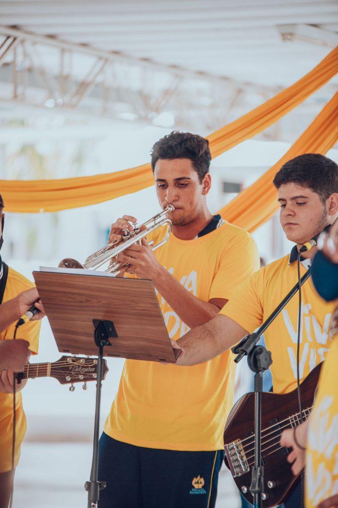 Alunos tocando guitarra, trompete e violão.