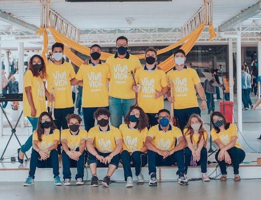 Imagem com alunos e funcionários usando camisetas amarelas com o título da campanha do Setembro Amarelo: Viva a Vida.