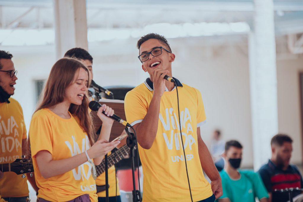 Dois jovens de camiseta amarela cantando para os colegas no pátio do colégio.