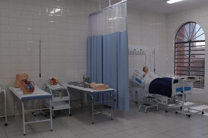 Camas e macas similares aos dos leitos hospitalares, com bonecos para aulas práticas.
